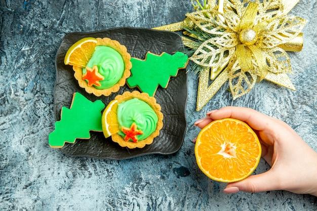 Vista dall'alto piccole torte biscotti dell'albero di natale sulla piastra nera ornamento di natale tagliato arancione in mano della donna sul tavolo grigio