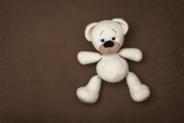 Top view of a small white bear cub lying on a brown background. beautiful knitted toy.