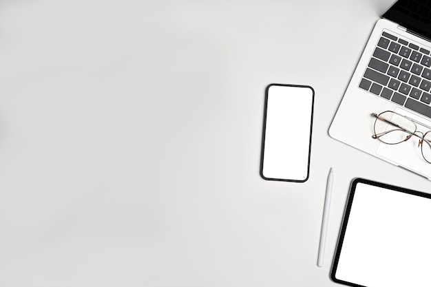 白い背景の上のビューのスマートフォン、ラップトップ、デジタルタブレット、メガネ。