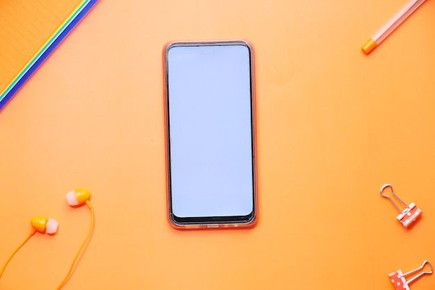 Top view of smart phone and office stationary on orange background