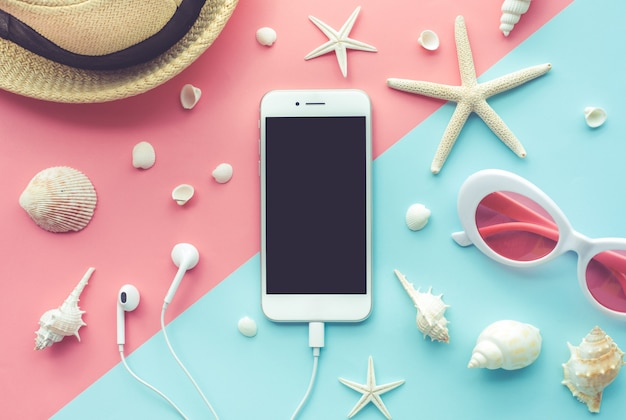 Top view of smartphone and element of vacation on color background.
