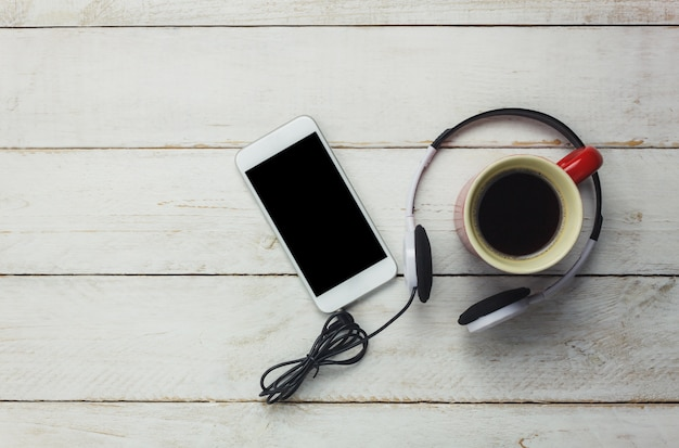 Top view smartphone and headphones with coffee cup
