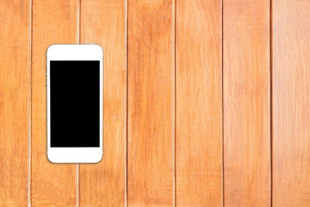 トップビュースマートフォンcopyspaceと木製のテーブルの上の黒い画面でテンプレートをモックアップします。