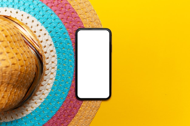 Top view of smartphone with mockup near colourful woman summer hat