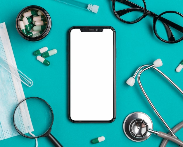 Вид сверху смартфон с таблетками и маской для лица