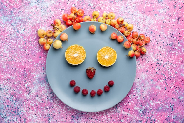 Top view smile from fruits inside plate on bright pink desk