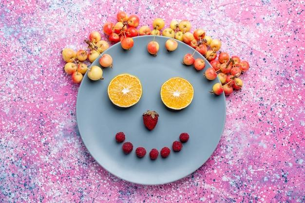 明るいピンクの机の上の皿の中の果物からの上面図笑顔