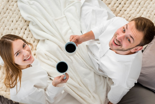 Top view of smiley couple holding coffee cups
