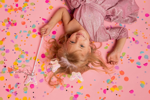 Top view of smiley girl in fairy costume with confetti