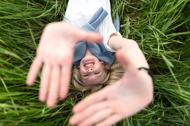 Top view of smiley woman posing in grass