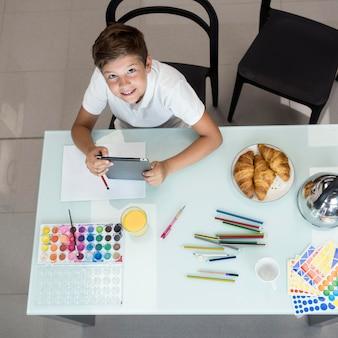 Вид сверху смайлик молодой мальчик держит планшет