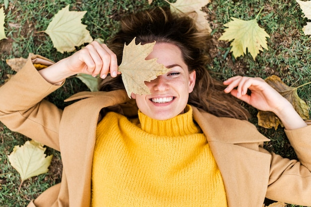 Top view smiley young woman staying on the ground next to autumn leaves