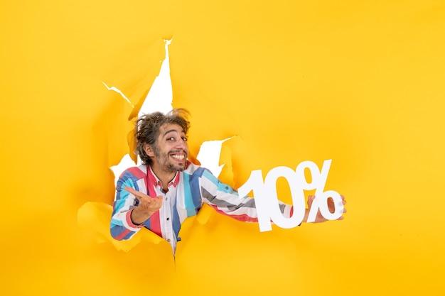 Vista dall'alto di un uomo barbuto sorridente che mostra il dieci percento in un buco strappato in carta gialla