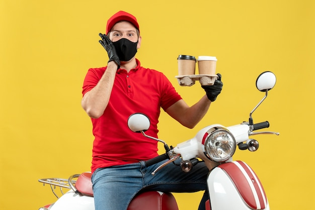 Top view of smiling confident delivery guy wearing uniform and hat gloves in medical mask sitting on scooter showing orders