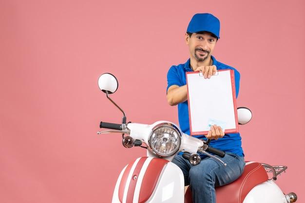 Vista dall'alto del corriere sorridente in maschera medica che indossa un cappello seduto su uno scooter che tiene un documento su una pesca pastello