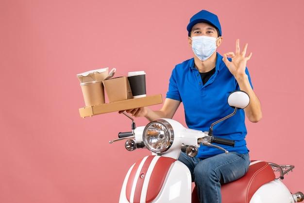 Vista dall'alto del corriere sorridente in maschera medica che indossa un cappello seduto su uno scooter che fa il gesto degli occhiali sulla pesca pastello pastel