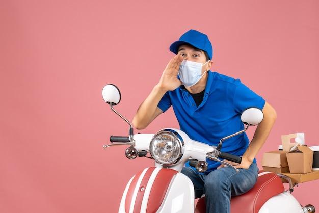 Vista dall'alto di un corriere sorridente in maschera medica che indossa un cappello seduto su uno scooter che chiama qualcuno su una pesca pastello