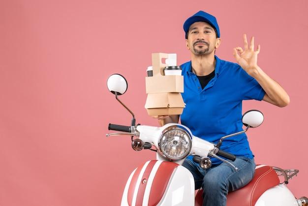 Vista dall'alto di un corriere sorridente che indossa un cappello seduto su uno scooter che tiene ordini facendo un gesto perfetto su una pesca pastello