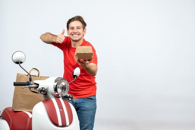 Vista superiore del fattorino sorridente in uniforme rossa in piedi vicino all'ordine di tenuta dello scooter e che fa gesto giusto sul muro bianco