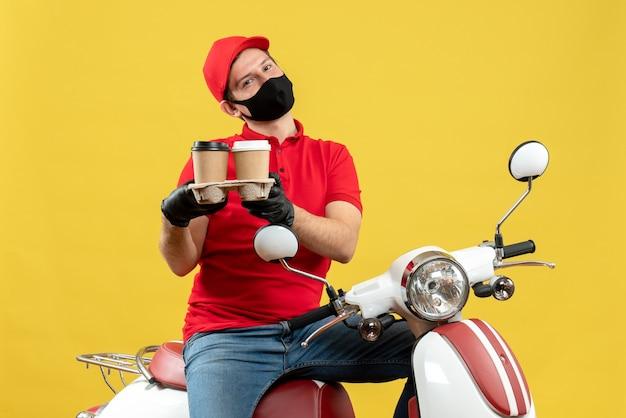 Vista superiore del fattorino sorridente che indossa guanti uniformi e cappello in mascherina medica che si siede sul motorino che dà gli ordini