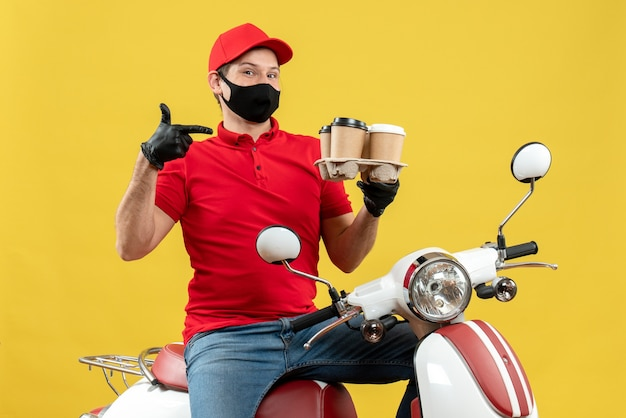 Top view of smiling delivery guy wearing uniform and hat gloves in medical mask sitting on scooter pointing order