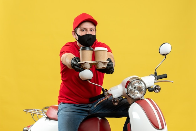 Top view of smiling delivery man wearing uniform and hat gloves in medical mask sitting on scooter giving orders