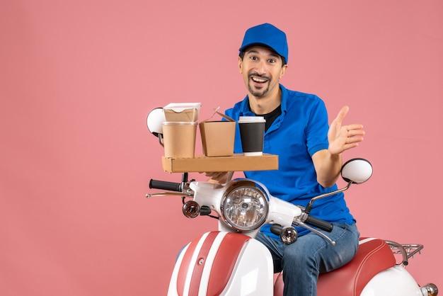 Vista dall'alto di un felice corriere sorridente che indossa un cappello seduto su uno scooter su una pesca pastello