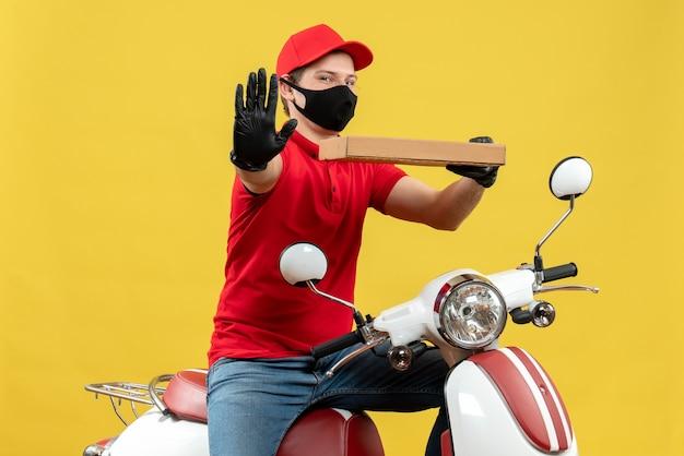 Vista superiore dell'uomo sorridente felice del corriere che indossa guanti rossi della camicetta e del cappello nella mascherina medica che si siede sullo scooter che mostra l'ordine che mostra cinque