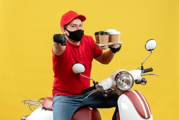 Vista superiore dell'uomo di consegna felice sorridente che indossa guanti uniformi e cappello nella mascherina medica che si siede sullo scooter che mostra gli ordini