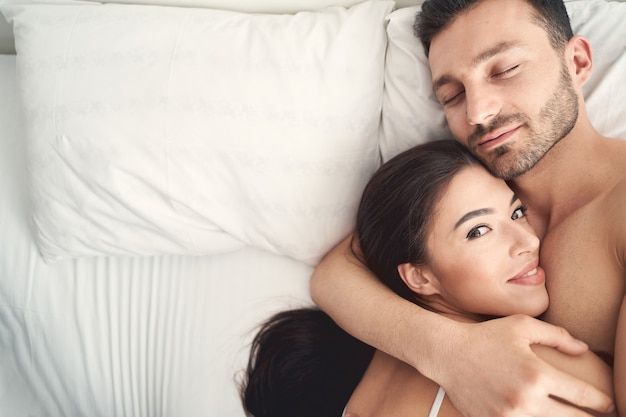 Top view of a smiling happy woman lying on her sleeping husbands chest in bed