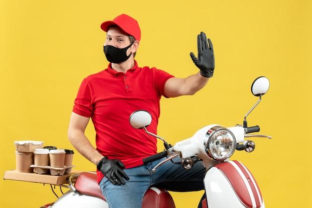 Vista superiore del giovane adulto felice sorridente che indossa la camicetta rossa e guanti del cappello nella mascherina medica che consegna l'ordine che si siede sullo scooter che mostra cinque sulla parete gialla