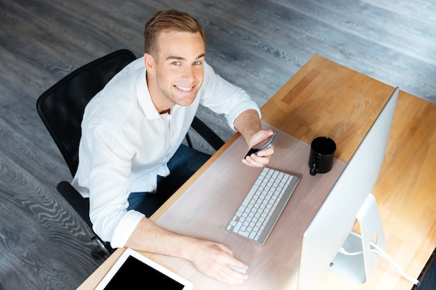 Top view of smiling relaxed young businessman sitting and using smartphone in office