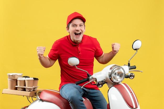 Vista superiore del giovane adulto sorridente che indossa la camicetta rossa e il cappello che trasporta l'ordine che si siede sullo scooter che si sente felice sulla parete gialla