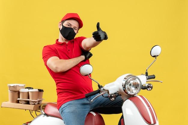Vista superiore del giovane adulto sorridente che indossa la camicetta rossa e guanti del cappello nella mascherina medica che trasporta l'ordine che si siede sullo scooter che fa il gesto giusto sulla parete gialla