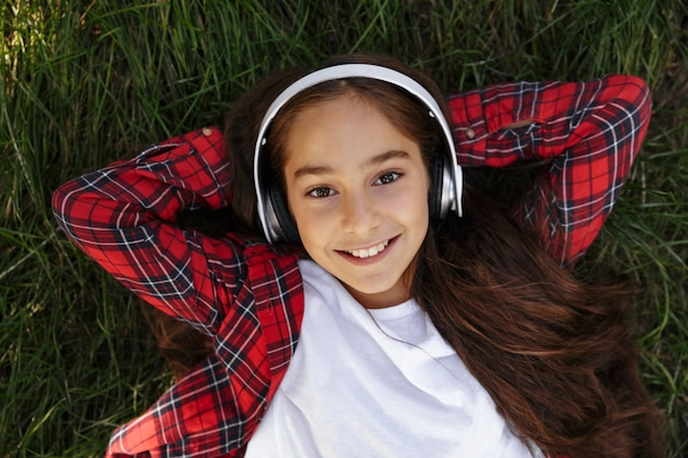 Top view of smiling young brunette girl lying on grass