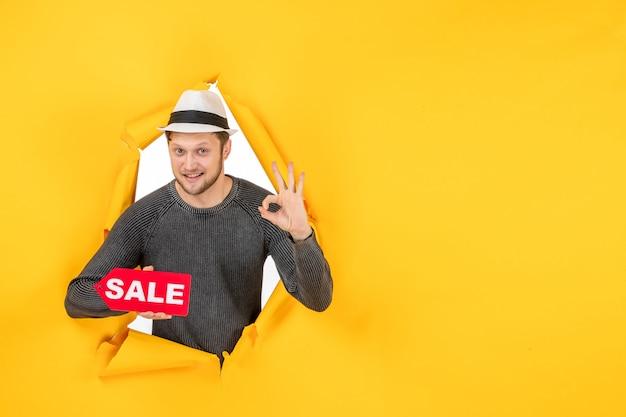 Vista dall'alto di un giovane ragazzo sorridente che tiene in mano un cartello di vendita e fa un gesto con gli occhiali in una parete gialla strappata yellow