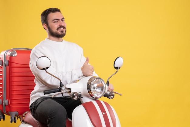 Vista dall'alto di un giovane ragazzo sorridente seduto in moto con la valigia sopra e che fa un gesto ok sul giallo