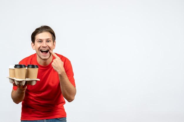 Vista dall'alto del giovane sorridente in camicetta rossa che tiene gli ordini che fanno il gesto di sorriso sulla parete bianca