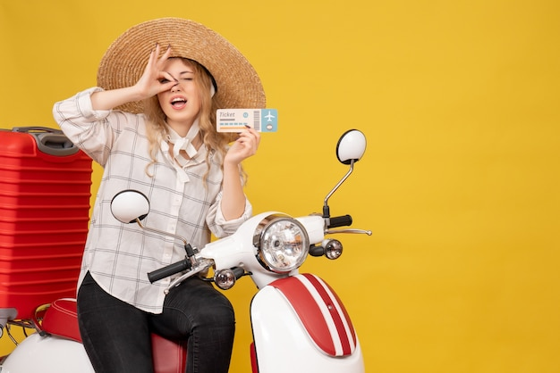 Top view of smiling young woman wearing hat and sitting on motorcycle and holding ticket making eyeglasses gesture on yellow