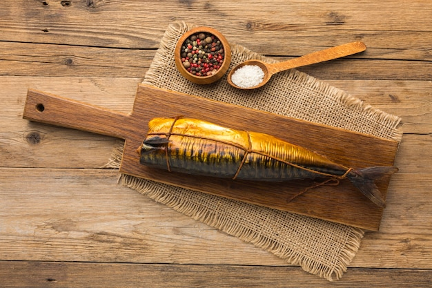 Top view smoked fish on wooden background