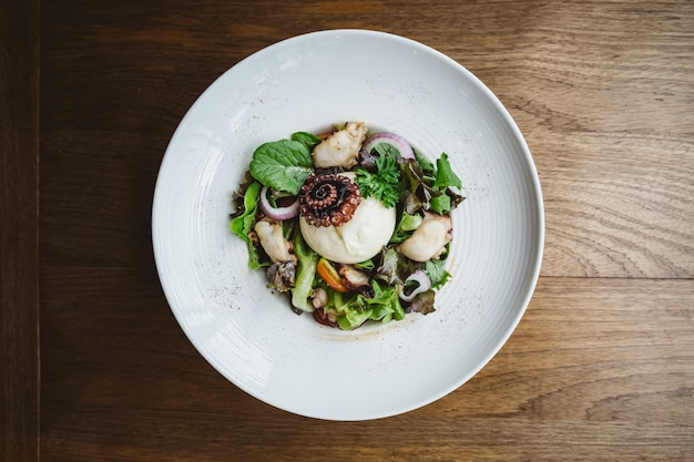 Top view of smoked galician octopus with burrata cheese, radish, green oak and tomato.