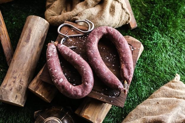 Вид сверху копченая колбаса на подносе с дровами и мешковины на траве
