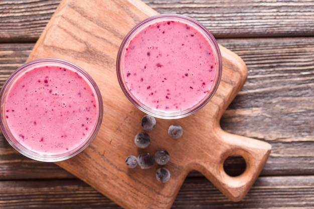 Top view smoothie glasses on cutting board with blueberries