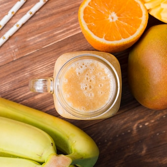 Top view smoothie jar with bananas and orange
