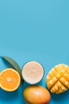 Вид сверху коктейль с манго и апельсином с копией пространства