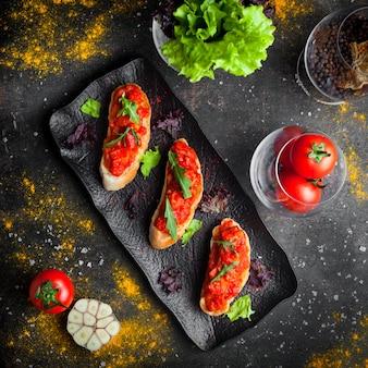 Закуска сверху и нарезанный хлеб сверху томатный салат и руккола в темной тарелке