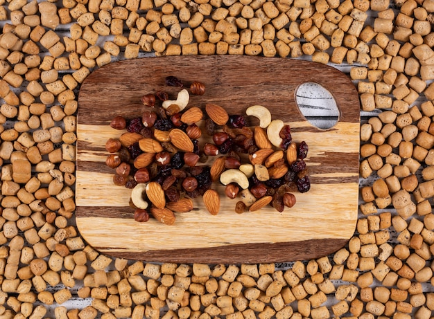 Top view of snacks as nuts, dried fruits on cutting board on crackers texture horizontal