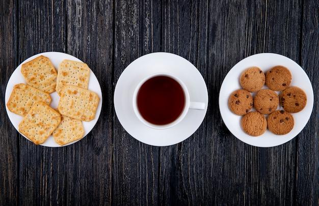 トップビュースナック塩味のクラッカーチョコレートクッキーと黒の木製の背景にお茶のカップ