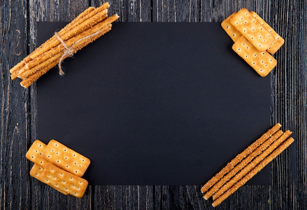 Top view snacks salty crackers and cracker sticks with copy space on black background