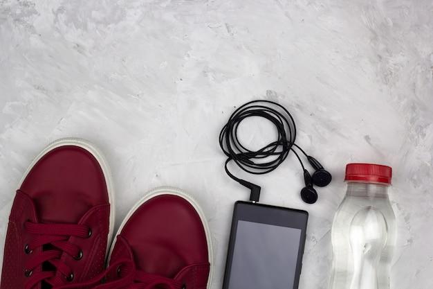 Вид сверху кроссовок смартфона с наушниками и бутылкой воды